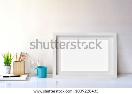 Mockup white poster frame, workspace and supplies. #1039228435