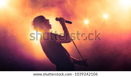 Singer holding a microphone stand and performing on stage Royalty-Free Stock Photo #1039242106