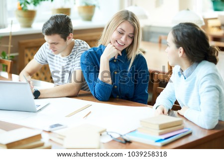 Cheerful blond-haired student with charming smile chatting animatedly with her friend while sitting at wooden table of library, their handsome groupmate wrapped up in doing homework #1039258318