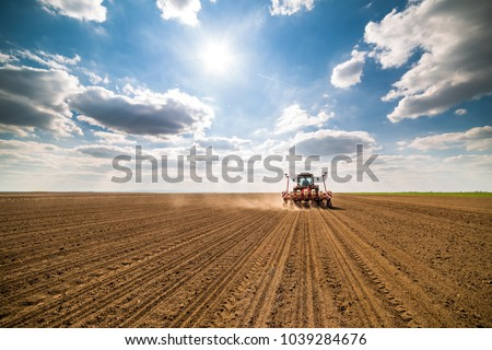 Farmer seeding, sowing crops at field. Sowing is the process of planting seeds in the ground as part of the early spring time agricultural activities. #1039284676