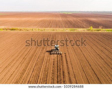 Aerial shot of a farmer seeding, sowing crops at field. Sowing is the process of planting seeds in the ground as part of the early spring time agricultural activities. #1039284688