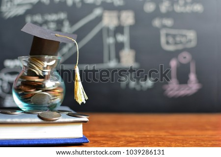 hat graduation model on coins saving for concept investment education and scholarships  #1039286131