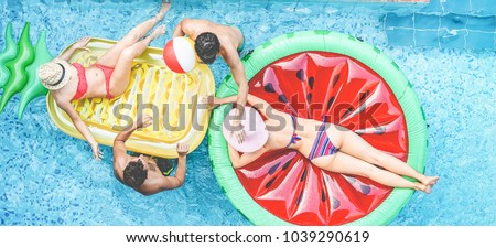 Happy friends playing with air lilo ball inside swimming pool - Young people having fun on summer holidays vacation - Travel, holidays, youth lifestyle, friendship and tropical concept #1039290619