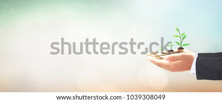 Return on investment concept: Businessman hands save holding stack of golden coin with small tree on blurred nature background Royalty-Free Stock Photo #1039308049