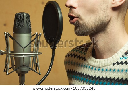 Radio dj concept. Profile portrait of handsome young man with blond hair hosting show live in studio. Close up. Indoor shot #1039333243