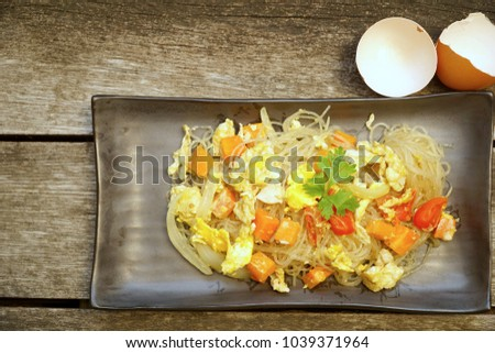 Vegetarian food of Thai fried vermicelli noodles with Eggs, Carrots, Tomatoes and Onions on black plate. Wooden background. Healthy and diet food. Still life food. Copy space. #1039371964