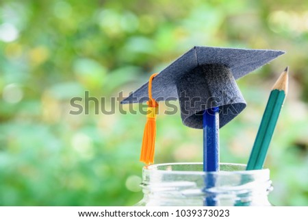 Education is the most powerful weapon or knowledge is power concept : Black graduation cap or hat with orange tassel on a pencil in a clear glass bottle, a green pencil with sharp tip points upward. #1039373023