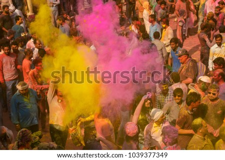 NANDGAON - Feb 25: People throw colors to each other during the Holi celebration at Krishna temple on February 25, 2018 in Nandgaon, India. Holi is the most celebrated religious festival in India. #1039377349