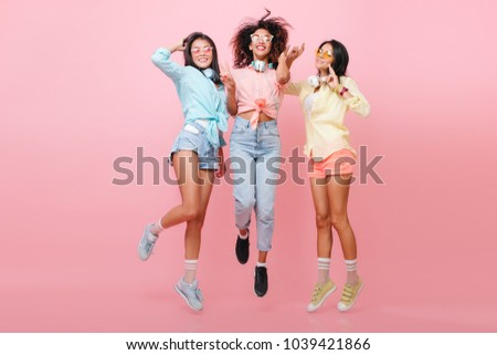Full-length portrait of enthusiastic african girl in black shoes posing between international friends in pink studio. Sporty asian woman in blue shirt jumping near stylish ladies. #1039421866