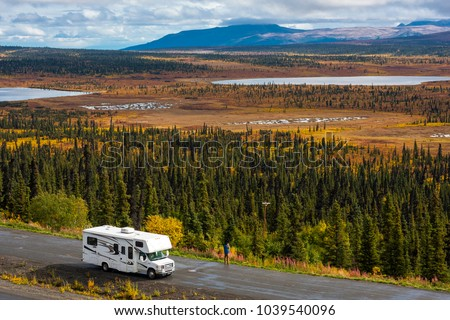 RV, motorhome, caravan parking next to a road in a parking lot in Alaska with spectacular, beautfiul background with lakes and conifer forest, blue sky and clouds #1039540096