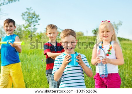 Kids group with toy water guns and other water containers #103962686