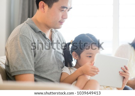 Father using touch screen tablet PC with daughter on sofa. Asian family at home, living lifestyle indoors. #1039649413
