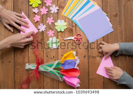 Parent and child hand playing with origami #1039693498