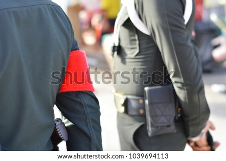 Red armband on Thai policeman. It's mean patrol officers.View from back and a blurry policeman standing to check everything at the celebration of the Chinese people.Concept is duty of police. #1039694113