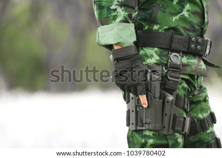 Soldier holding gun weapon and waring armor uniform. The military is responsible for maintaining the territory. #1039780402