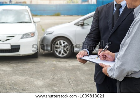 Insurance Agent examine Damaged Car and customer filing signature on Report Claim Form process after accident, Traffic Accident and insurance concept. #1039813021