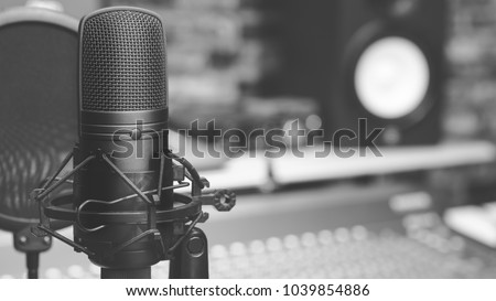black and white condenser microphone on audio mixing board & studio monitor speakers background. recording concept