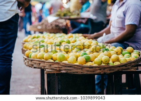 lemons and lime in a large wicker basket on the market in India at summer day #1039899043