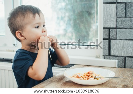 A beautiful cheerful child eats pasta with his hands, spaghetti all dirty #1039918096