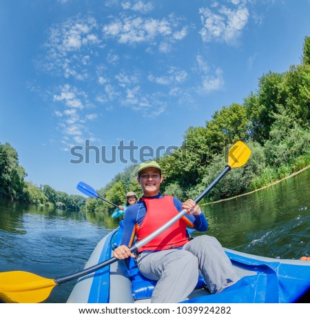 Active happy family. Girl with her mother having fun together enjoying adventurous experience kayaking on the river on a sunny day during summer vacation #1039924282