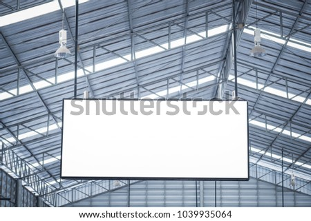 White blank advertising billboard hanging on high metal ceiling background ready for sales or posted new advertisement concept installed at city building area