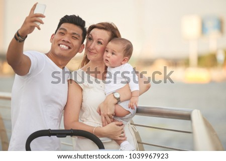 Cheerful multi-ethnic family taking selfie together #1039967923