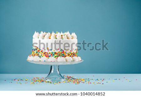 White Birthday cake with colorful Sprinkles over a blue background. Royalty-Free Stock Photo #1040014852