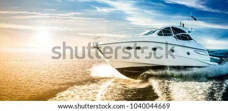 Luxurious motor boat sailing the sea at dawn Royalty-Free Stock Photo #1040044669