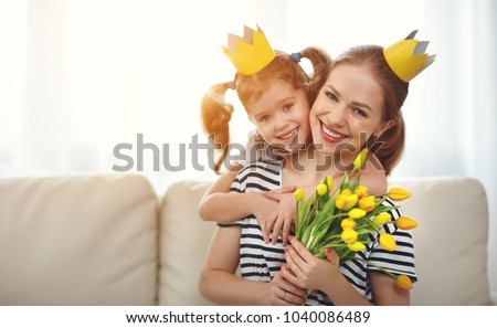 happy mother's day! mother and child daughter in crowns and with flowers yellow tulips