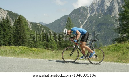 Pro road cyclist enduring a difficult mountain ascent on his cool bicycle. Determined Caucasian sportsman looks down and grits his teeth as he ascends a challenging mountain in the hot summer sun. #1040095186