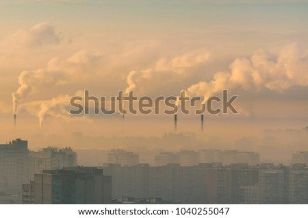 Urban landscape smoked polluted atmosphere from emissions of plants and factories, view of pipes with smoke and residential apartment buildings. Royalty-Free Stock Photo #1040255047
