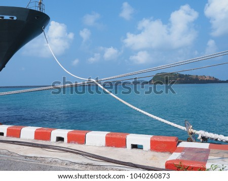 Cargo ships are parking at the pier and blue sky background. #1040260873