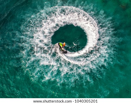 People are playing jet ski at sea during the holidays. And beautiful nature backdrop. #1040305201