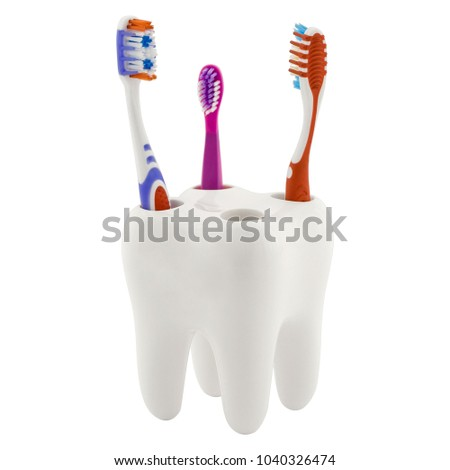Toothbrush holder in form of tooth with three toothbrushes. One children and two adult. Isolated on whitebackground. #1040326474