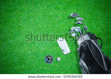 High angle view of golf bag, golf club, gloves and golf ball, with beautiful green lawn floor and golf hole as background.With space to write the text. #1040366581
