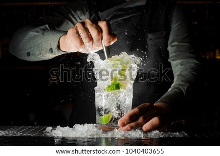 Bartender squeezing juice from fresh lime in a glass using a citrus press and splashing it out making an alcoholic cocktail #1040403655