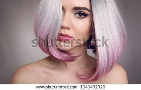 Colored Ombre bob hair extensions. Beauty Blonde Model Girl with short pink hairstyle isolated on gray background. Closeup woman portrait. #1040432320