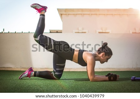 Slim young woman in sportswear doing donkey kick exercise,while kneeling on the floor and raising one leg up outdoors. Royalty-Free Stock Photo #1040439979