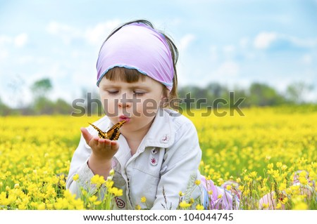Little cute girl in a field of beautiful yellow flowers holding a butterfly on the palms and blowing on it.