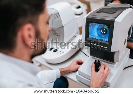 Handsome male doctor  ophthalmologist is checking the eye vision of attractive young woman in modern clinic. Doctor and patient in ophthalmology clinic. #1040460661
