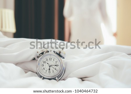 Alarm clock standing on bedside table has already rung early morning to wake up woman is stretching in bed in background.Relaxing concept. #1040464732