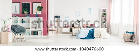 Grey armchair and pink wall in spacious bedroom interior with blue blanket on bed next to a wooden lamp #1040476600