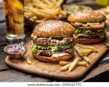 Hamburgers and French fries on the wooden tray. #1040567770
