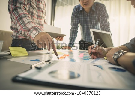 Brainstorming Group of people Working Concept. Business team brainstorming. Marketing plan researching. Paperwork on the table, laptop and mobile phone. #1040570125