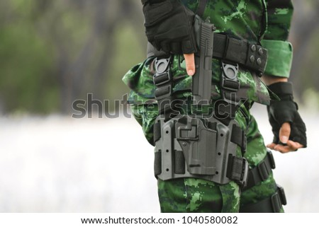 Close-up soldier standing outdoors. The military is responsible for maintaining the territory. Soldier holding gun weapon and waring armor uniform. #1040580082