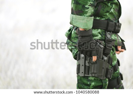 Close-up soldier standing outdoors. The military is responsible for maintaining the territory. Soldier holding gun weapon and waring armor uniform. #1040580088