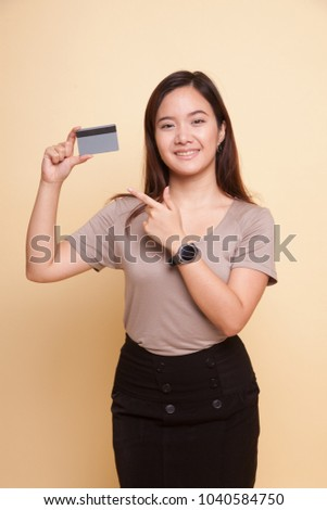 Young Asian woman point to a blank card on beige background #1040584750