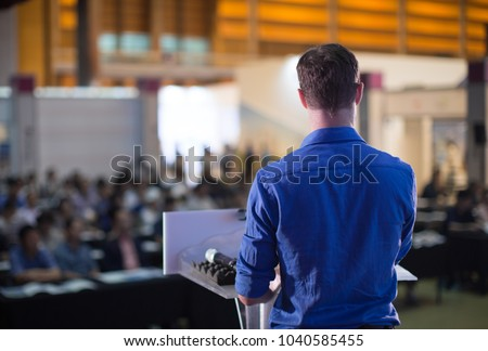 Professional Man on Stage Giving Business Presentation #1040585455