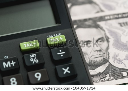 Closed up shot of TAX minus / plus buttons with text TAX RATE on calculator with background of US Dollar banknotes, United States government tax calculation. #1040591914
