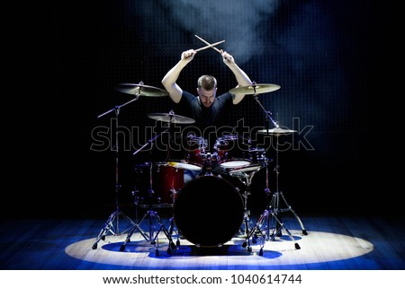 Drummer playing the drums with smoke and powder in the background #1040614744